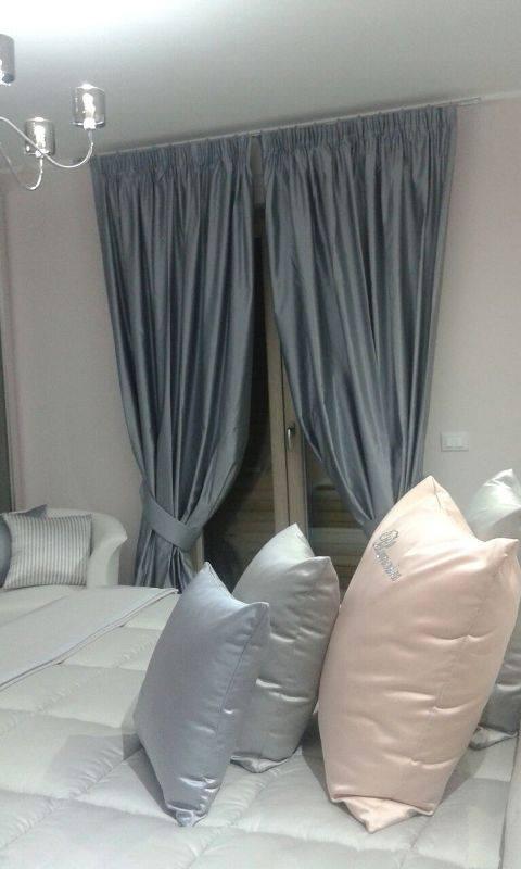un letto con dei cuscini con le federe satinate e una finestra con le tende grigie