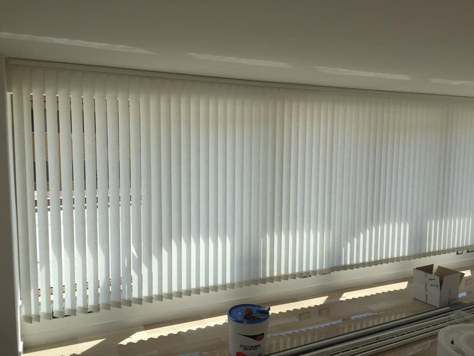 una finestra lunga con le tende da ufficio