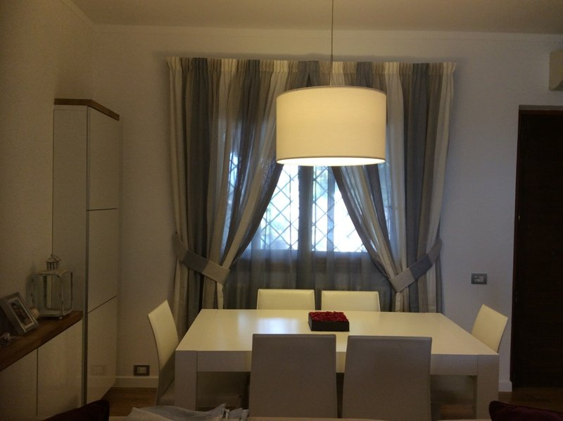 una cucina con un tavolo e una finestra con le tende di color grigio e avorio