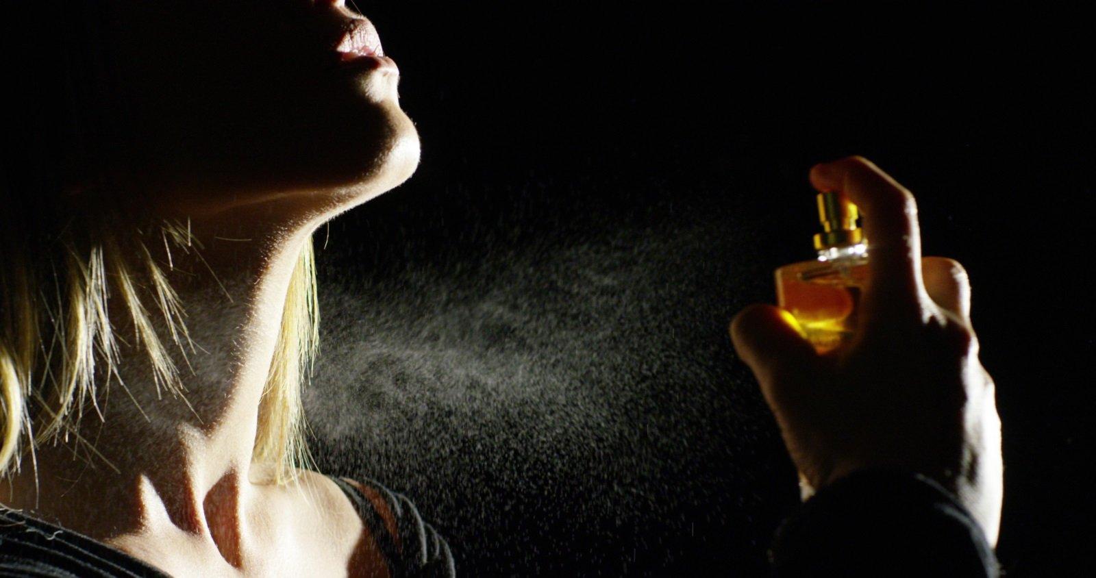 donna che spruzza del profumo