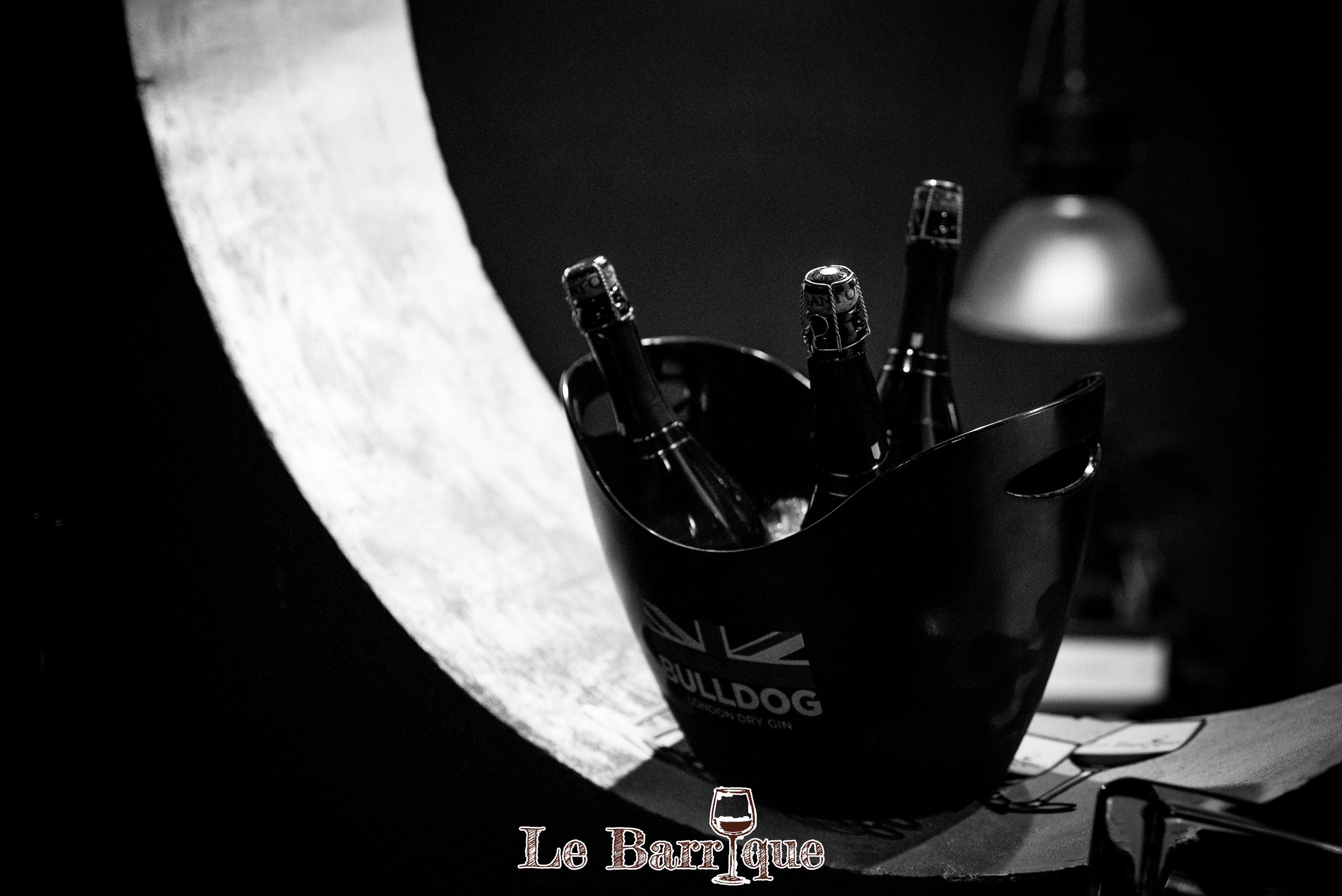 immagine bianco e nero di un portaghiaccio con tre bottiglie di champagne all'interno