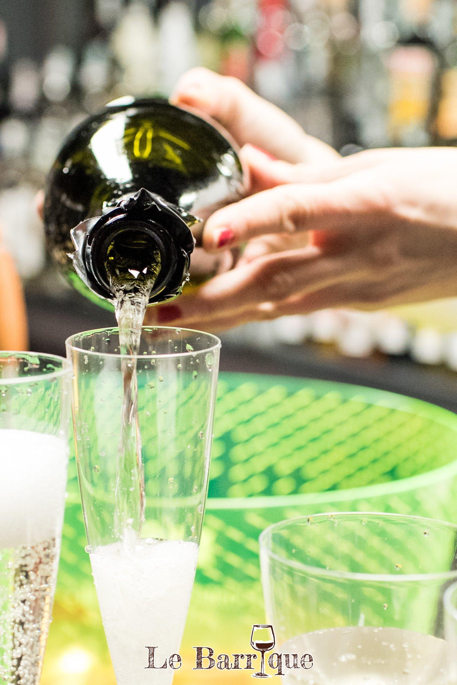 mani del barista che versano champagne in un bicchiere