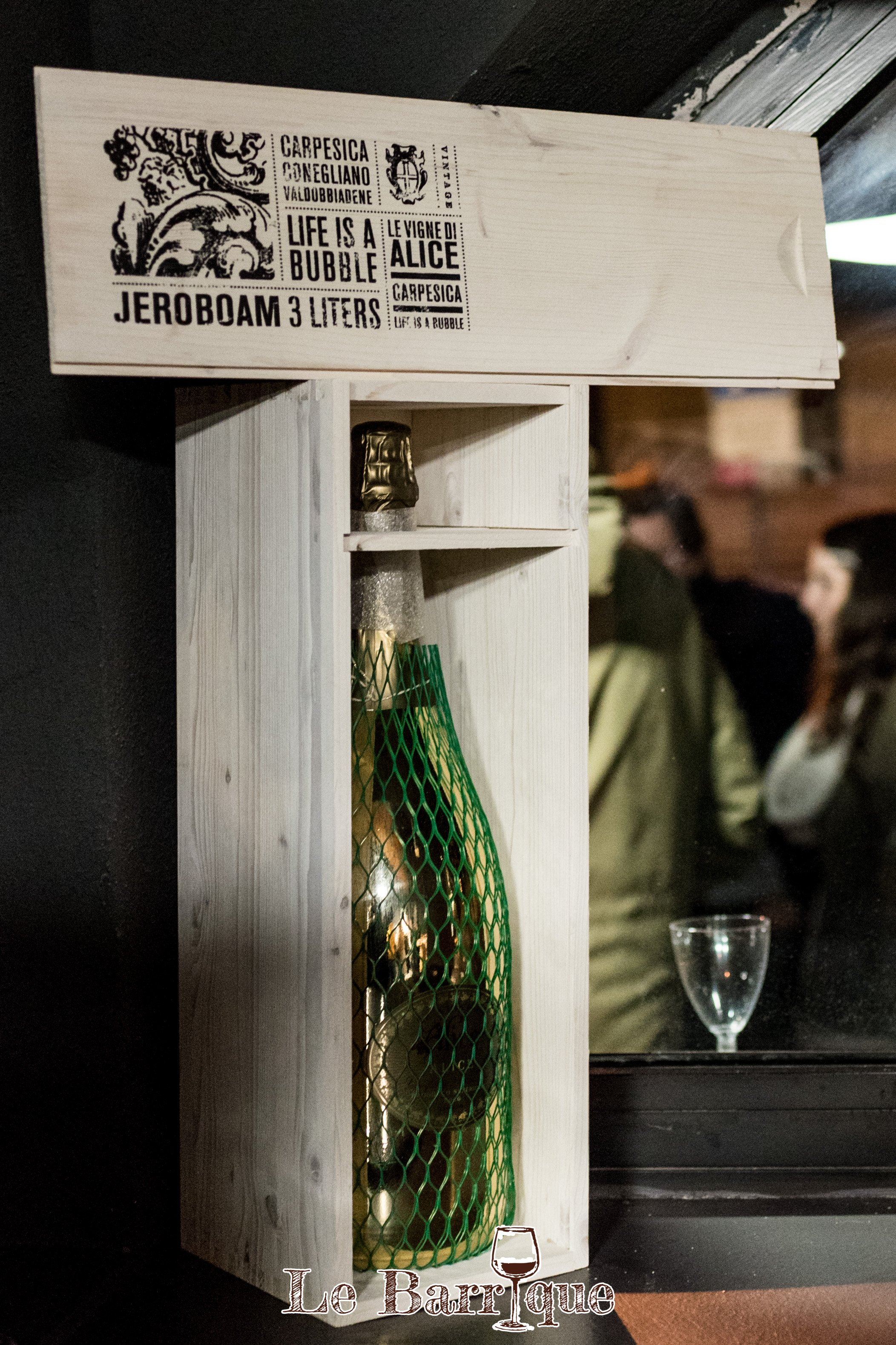 Bottiglia verde di Champagne in un portabottiglie di legno