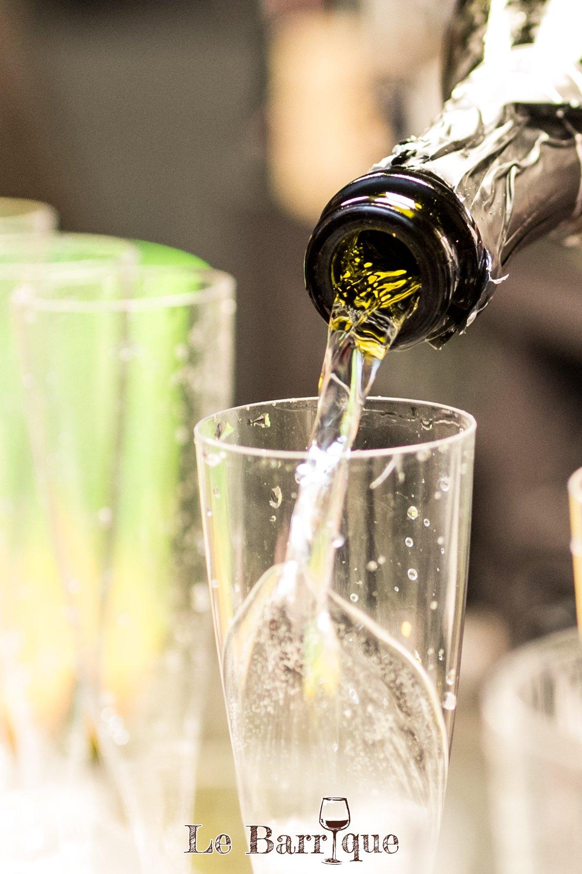 Bottiglia di champagne che versa lo stesso in un bicchiere