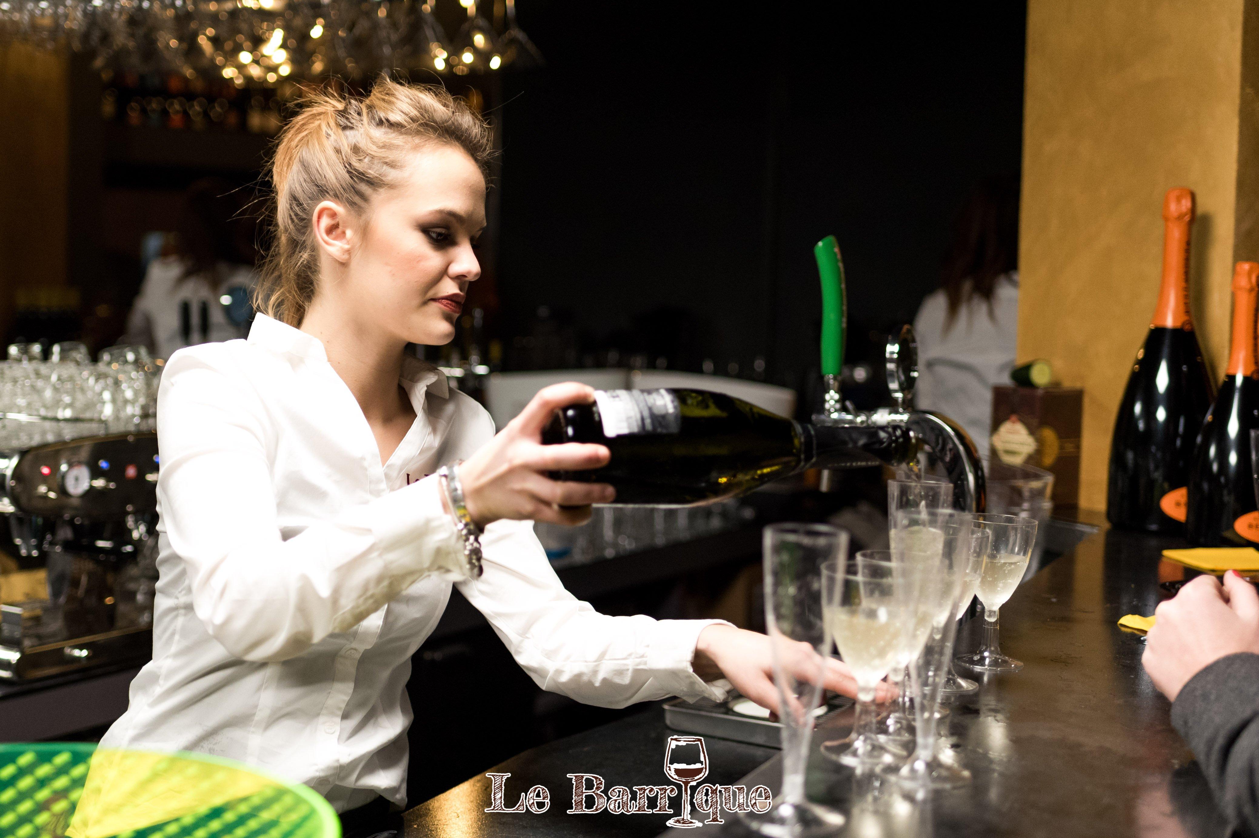 Ragazza barista bionda che versa champagne in bicchieri