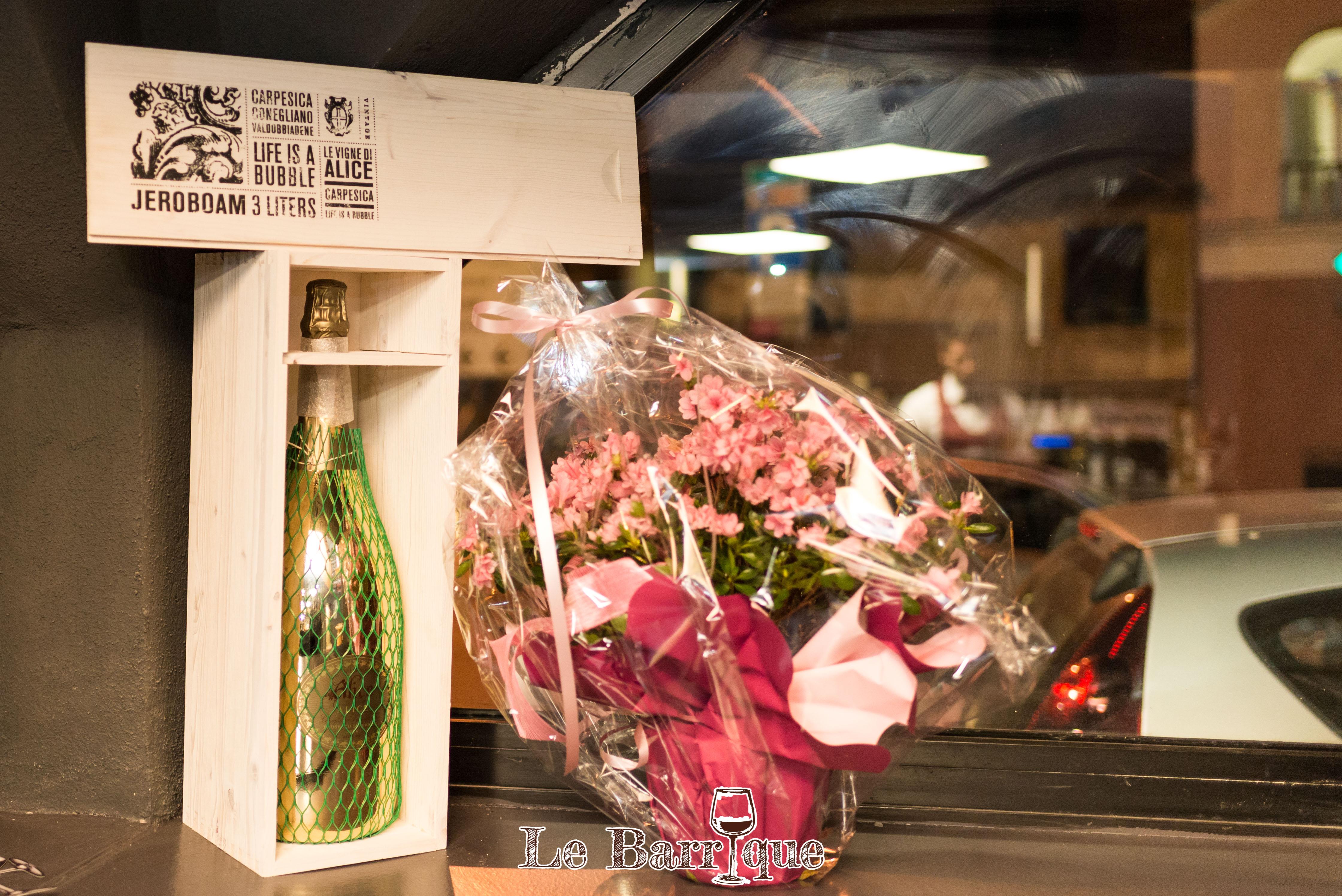 Bottiglia di champagne in cornice di legno con fiori sul bancone