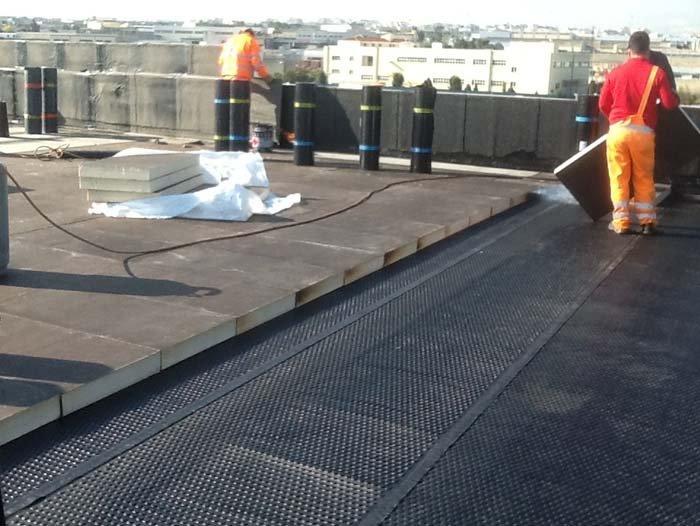 operai sistemano dei pannelli sul tetto in polistirene espanso per isolamento termico