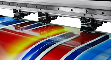 una stampante industriale e sotto un foglio a colori rosso,blu,bianco,nero e giallo in fase di stampa