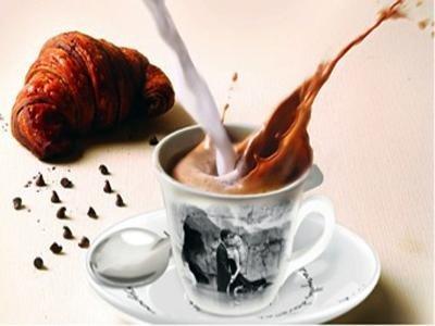 Latte saltando nel cafe accanto a un cornetto