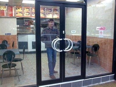 A man exiting through a black aluminium double fronted door