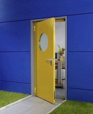 A bright yellow door situated against blue walls with a nautical styled porthole window