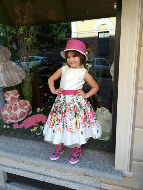 bambina con abito bianco e a fiori davanti una vetrina di un negozio
