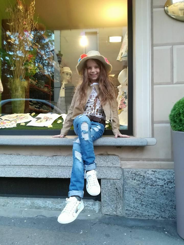 bambina seduta su una vetrina di un negozio
