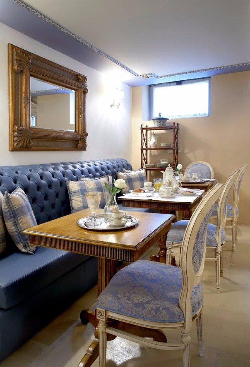 tre tavolini in legno e un divano di pelle di color azzurro