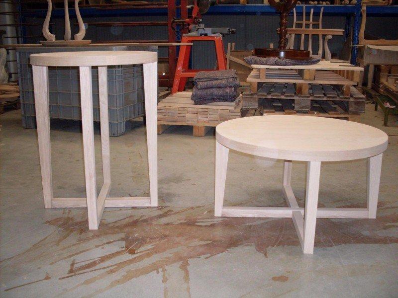 due tavolini in legno chiaro e altri mobili in un magazzino