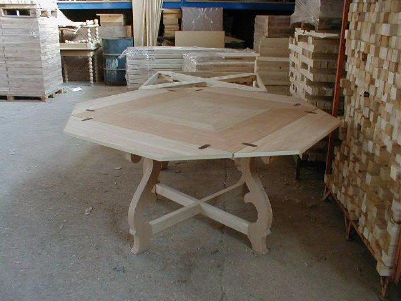 un tavolino in legno e accanto un' asse di legno in un magazzino