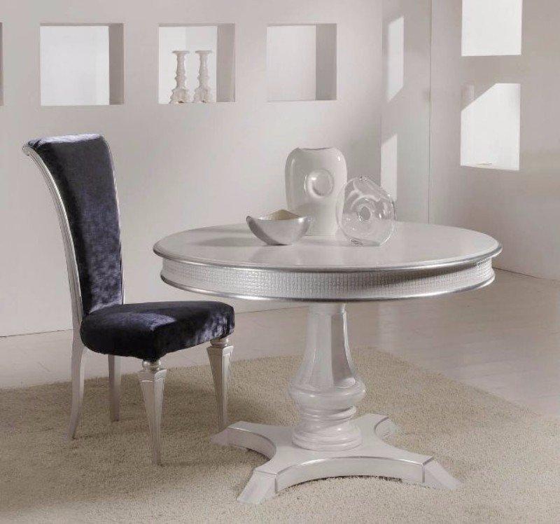 un tavolino rotondo di color argento e una poltrona rivestita in velluto
