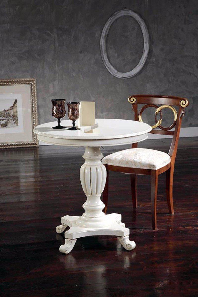 un tavolino rotondo di color bianco e una poltrona in legno scuro con disegni dorati