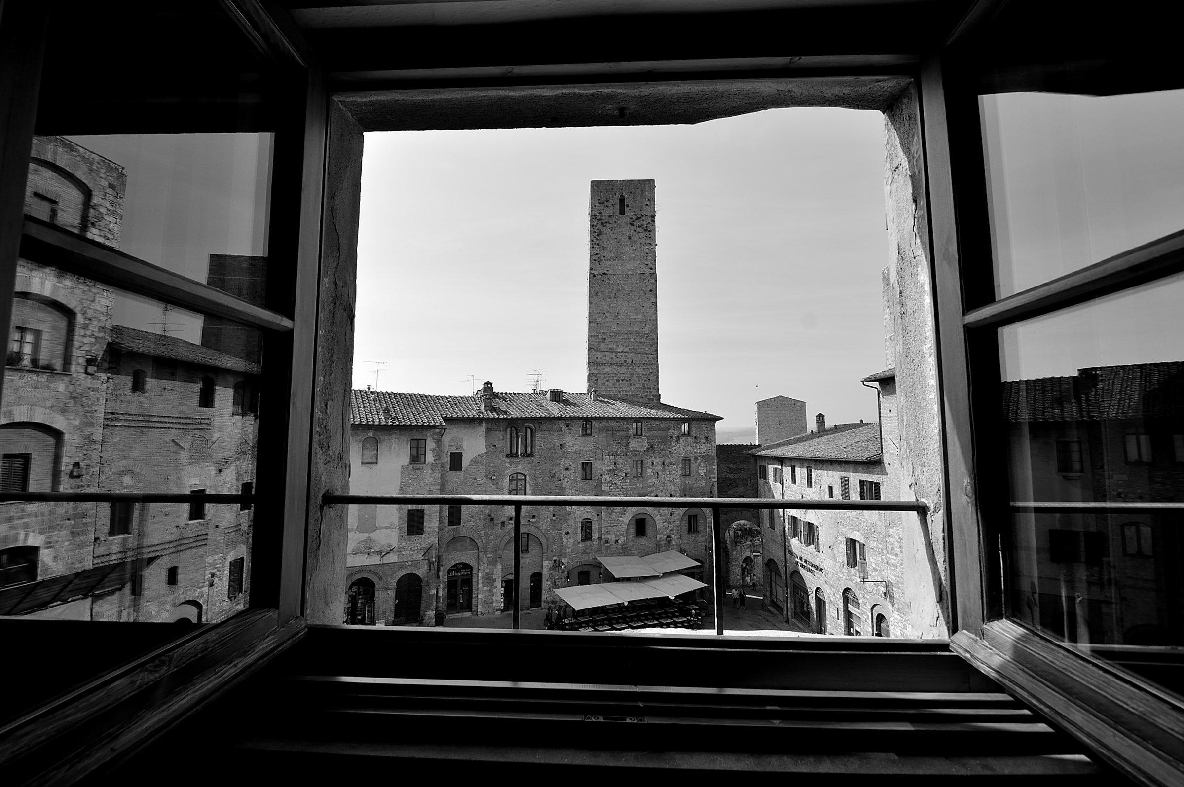 Vista dal un balcone, in bianco e nero, di una torre in mezzo ad una piazza storica