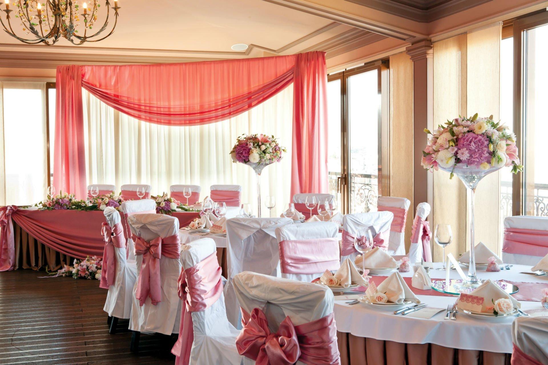 dei tavoli con dei vasi di fiori apparecchiati per una cerimonia