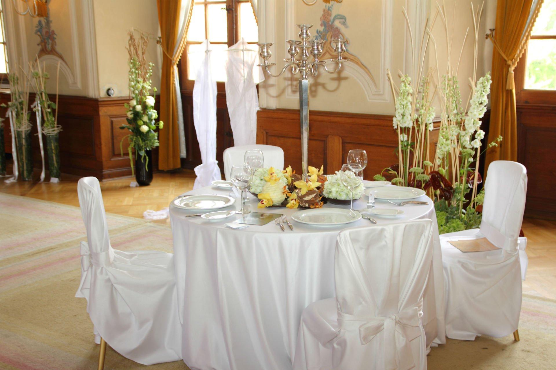 un tavolo apparecchiato per una cerimonia con piatti, fori e un candelabro