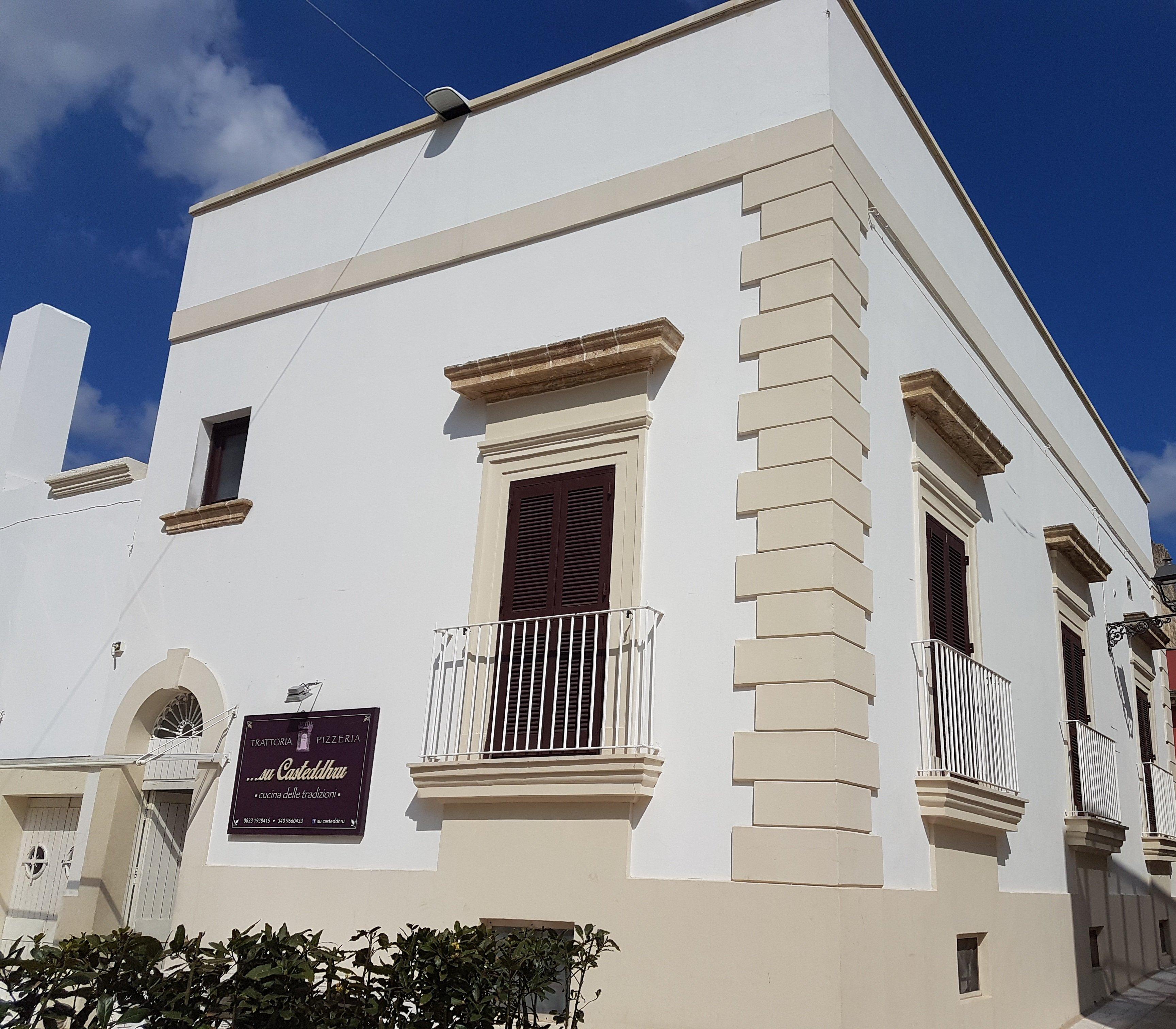 facciata esterna color bianco sporco della  CASTEDDHRU TRATTORIA PIZZERIA