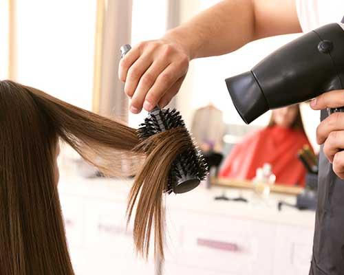 una mano con una spazzola e un fon mentre asciuga i capelli a una donna