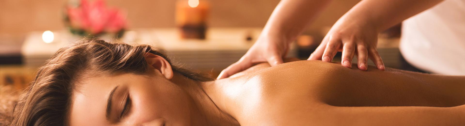 due mani mentre massaggiano la schiena di una donna
