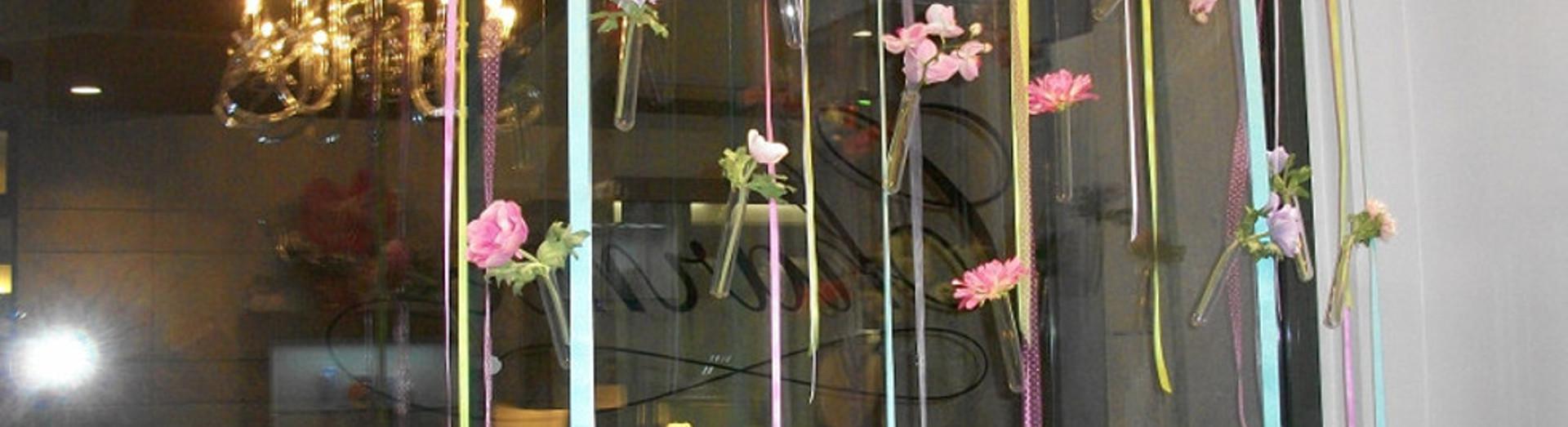 una vetrina con dei nastri colorati e decorazioni con dei fiori