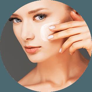 una donna mentre applica una crema sulle guance