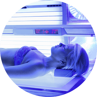 una donna sdraiata su un lettino in una cabina abbronzante
