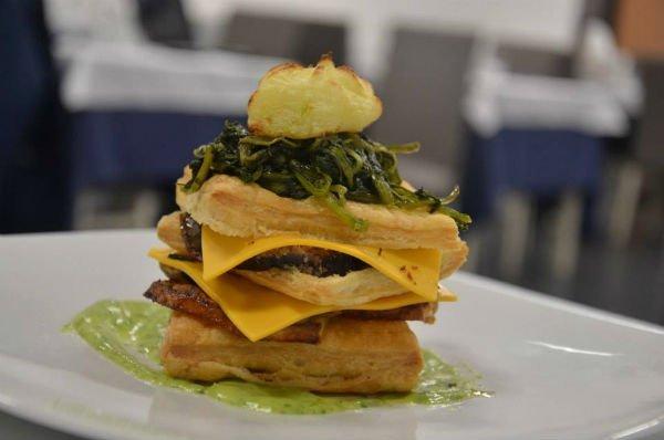 un sandwich con pasta sfoglia, spinaci, carne e formaggio