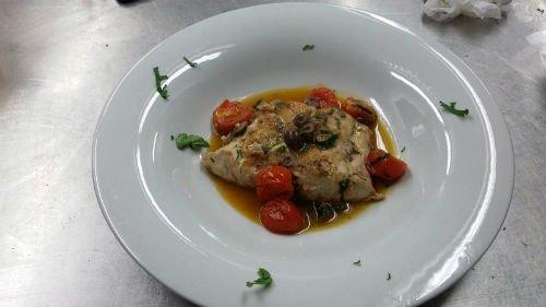 un piatto a base di pesce e pomodorini