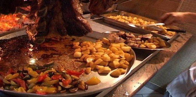 Dei vassoi grandi con della carne, patate e verdura