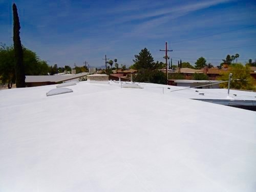 Roofer builder worker with pulverizer spraying paint
