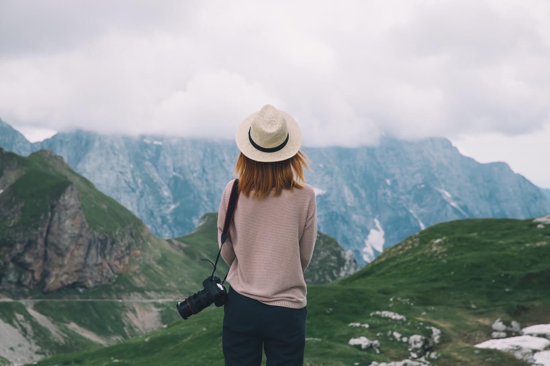 una ragazza che guarda un paesaggio di montagna