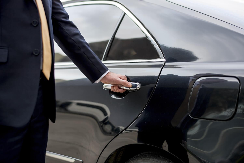 persona che apre la porta di una macchina nera