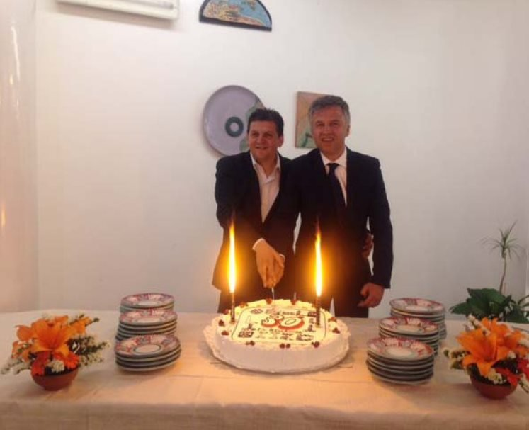 I fratelli Bellacosa davanti ad una torta con due candele accese per festeggiare i trenta anni di attività
