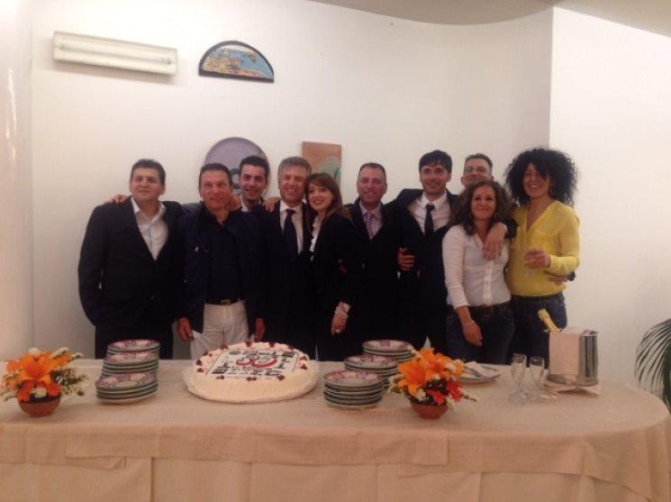 foto di gruppo del team davanti alla torta per i 30 anni di attività dei Bellacosa