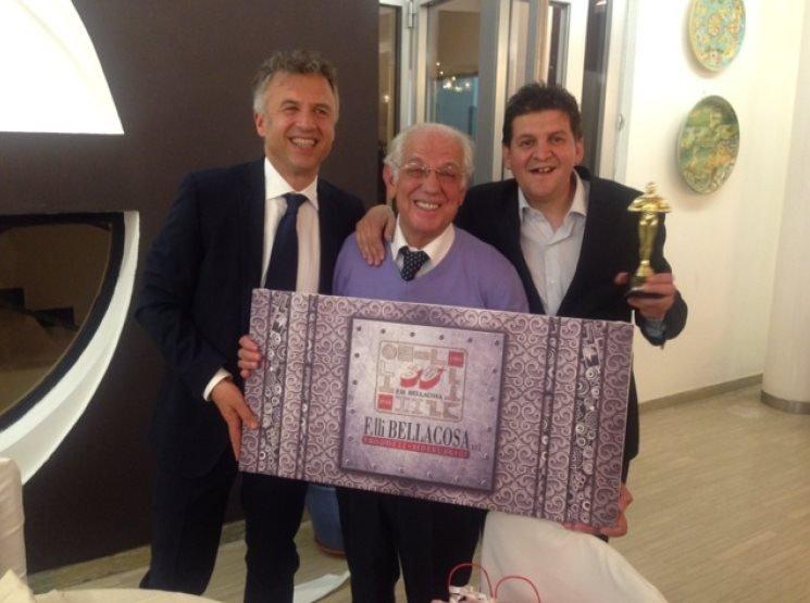 Tre eleganti manager dell'azienda che reggono una targa celebrativa ed un trofeo
