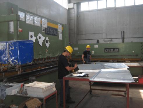 due operai con elemetto giallo di protezione impegnati nella produzione di lamiere