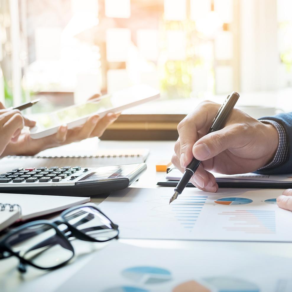 una mano di un uomo con una penna in mano e dei documenti su un tavolo