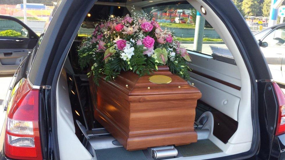 cofano con addobbo floreale dentro un carro funebre
