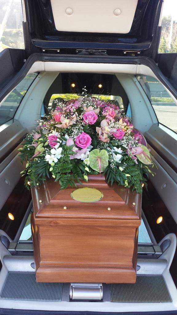 interno di un carro funebre con una bara in legno e sopra dei fiori bianchi e rosa