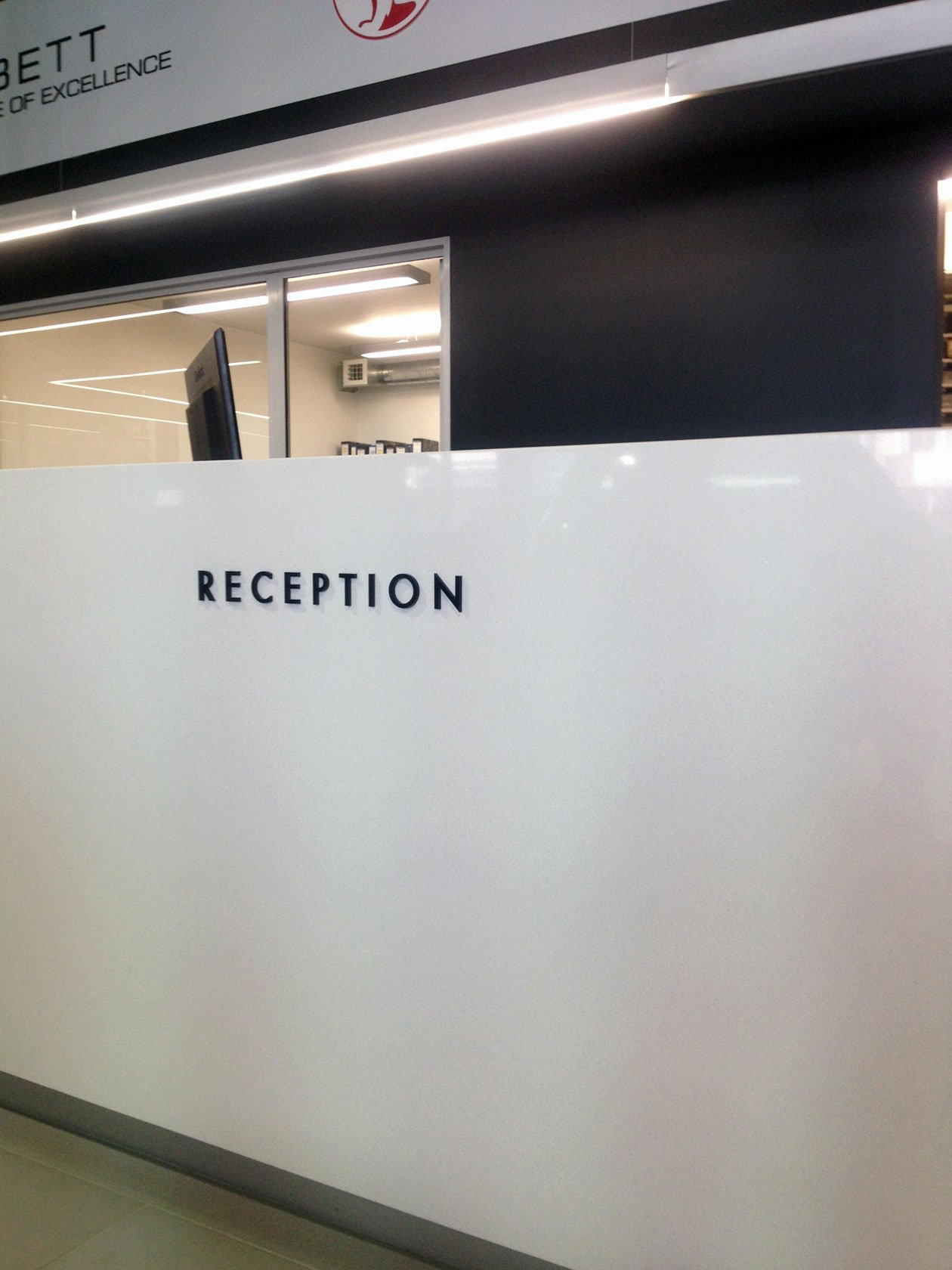 10mm thick laser cut black acrylic letters installed onto reception counter