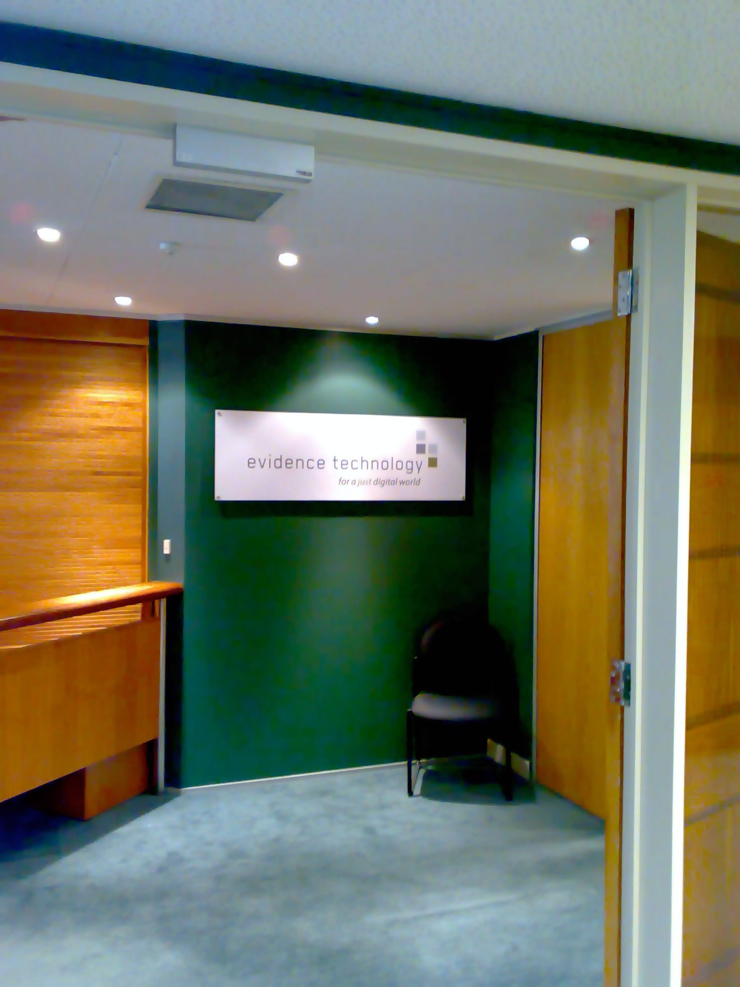 Perspex sign installed on office wall using sign mounts