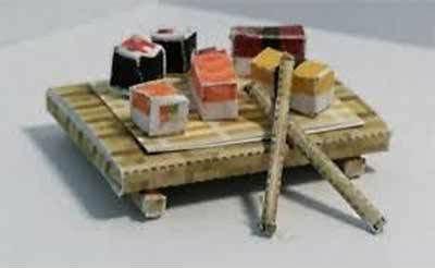 Piatto di legno con sushi e due bacchette di legno
