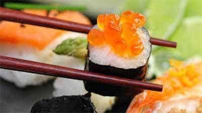 Prendendo una porzione di sushi con i bacchette