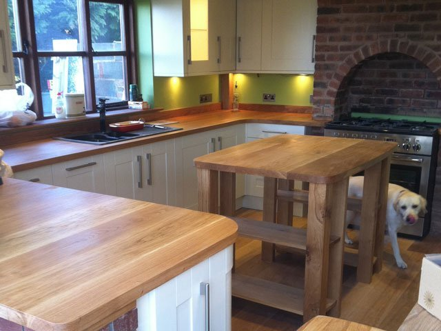 A kitchen with bespoke timber cabinets and a table all constructed by B and P Joinery in Worcester