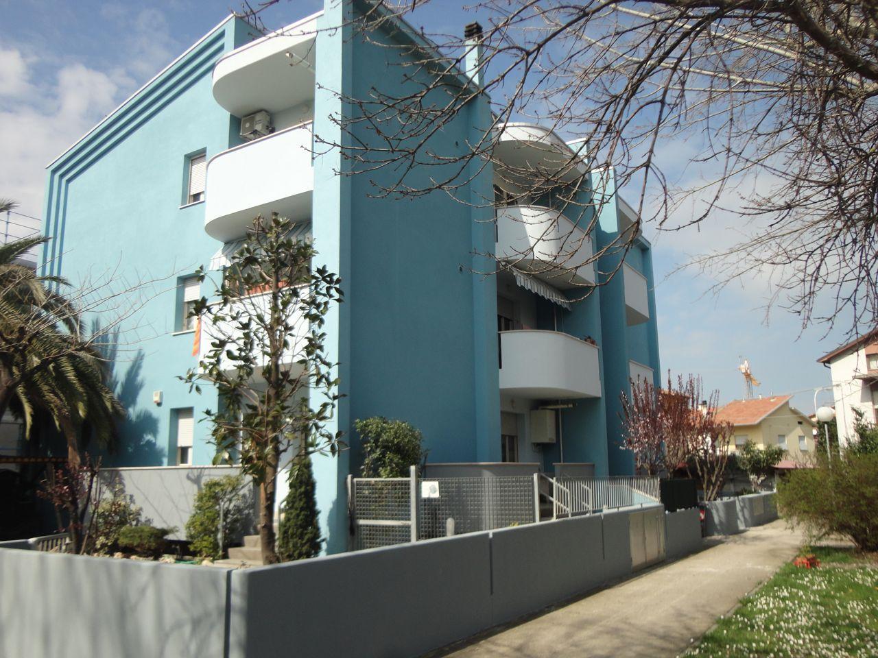 Edificio residenziale circondato da giardino privato dipinto di blu e bianco